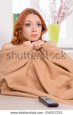 Red hair beauty. Beautiful red hair woman sitting on the couch and looking scared - stock photo