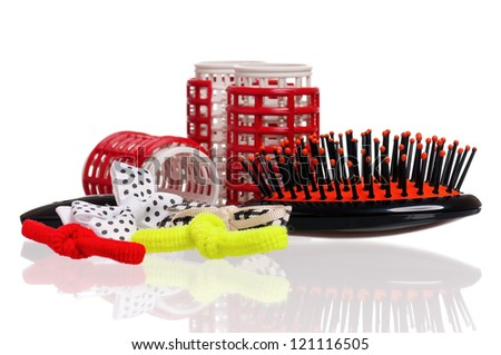 Red hair curlers and hairbrush isolated on white background - stock photo