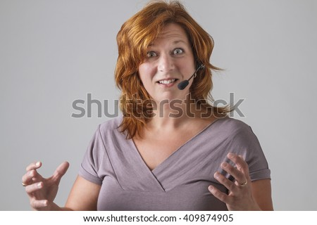 red hair female phone agent with headset with angry expression - stock photo
