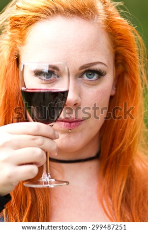 Red hair girl in pin-up style holding a glass of wine
