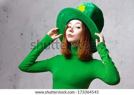 Red hair girl in Saint Patrick's Day leprechaun party hat having fun isolated on grey grunge background - stock photo