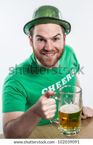 Red hair Irish guy on Saint Patrick's day drinking in bar with green hat clothes mug of golden beer