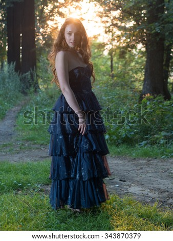 Red hair russian girl with freckles in dress posing in forest