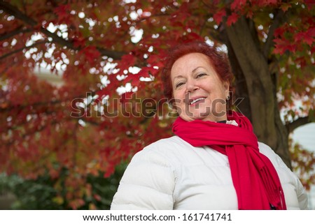 Red hair senior lady under the tree with red leaves looking at you happily with her red scarf and white coat