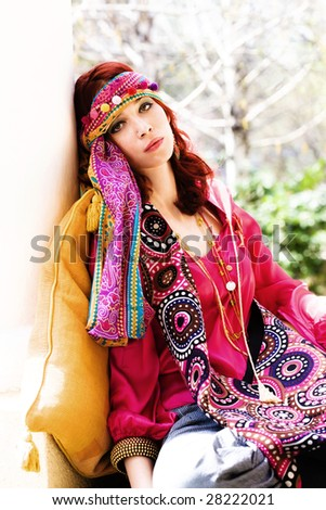 red hair woman in colorful clothes resting on terrace - stock photo