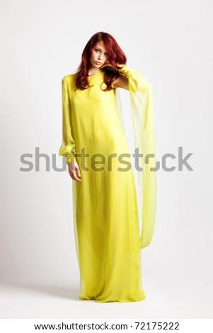 red hair woman in long elegant stylish yellow dress, full body shot, studio shot - stock photo