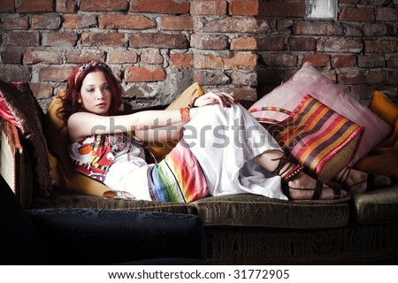 red hair woman in summer clothes resting on sofa - stock photo