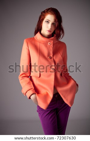 red hair woman in winter jacket portrait, studio shot