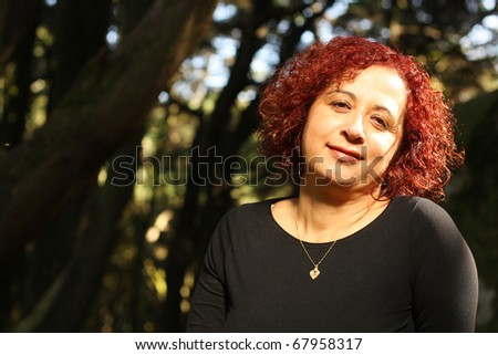 Red hair woman standing outdoors in a beautiful green forest