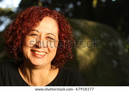Red hair woman standing outdoors in a beautiful green forest - stock photo