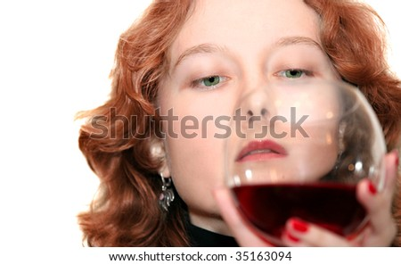 Red-haired and green-eyed woman looking at her glass of wine