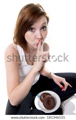 red haired attractive  woman in her 20's shushing with her finger and secretly eating a chocolate donut on a white background - stock photo