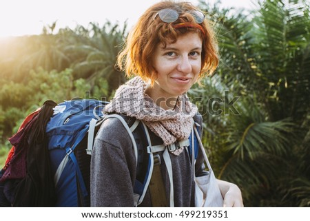 Red haired beautiful girl with her backpack, smiling (Malaysia).