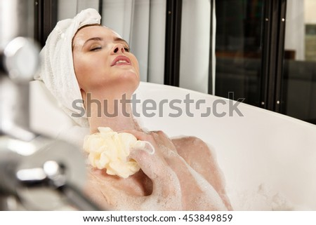 Red-haired beautiful young woman with a towel on her head after bath. Concept of care of body. - stock photo