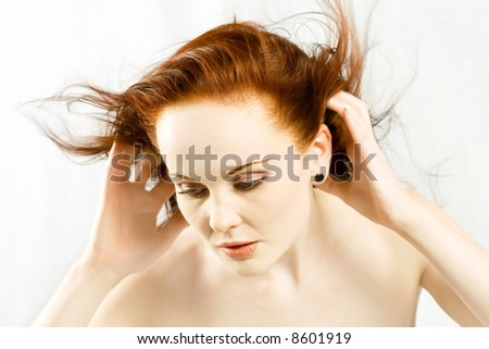 Red haired beauty looks down while hair is blown around