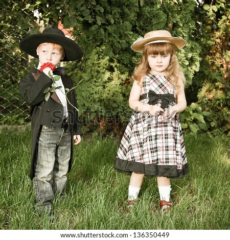 red-haired boy in a frock coat and a girl in a checkered dress, red rose. Declaration of love. - stock photo