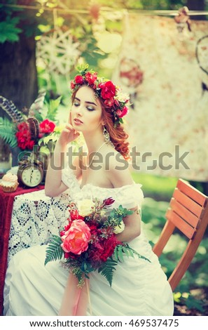 Red-haired bride in a beautiful wreath for the decorated table, summer wedding in the style of boho