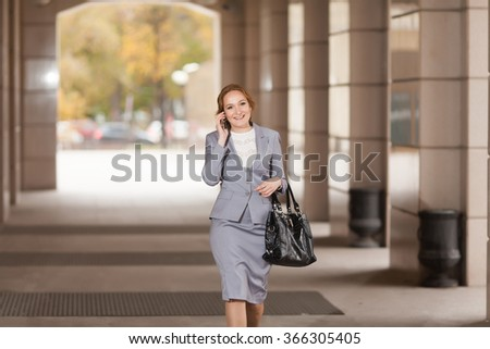Red haired business women walking and talking by phone on smooth background - stock photo