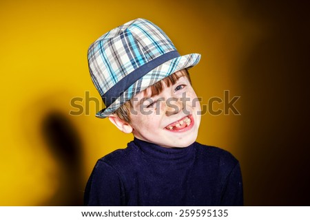 Red-haired expressive preschooler boy close-up emotional portrait, isolated on yellow - stock photo