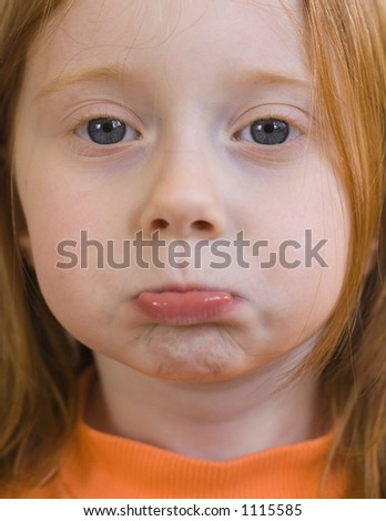 Red-Haired four-year-old girl with a pouting face.  Focus on eyes. - stock photo