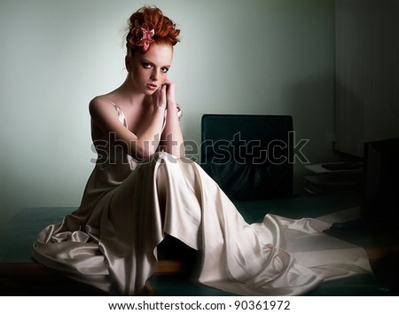 Red haired freckled  girl in ivory long dress on office desk sitting - series of photos