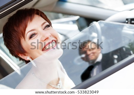 Red-haired funny bride in the car smiling groom.  Woman 35 years. Wedding.
