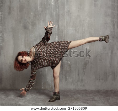 red-haired girl in a big knitted sweaters and boots standing on one leg, the spread hands on the background of a gray textured wall. - stock photo