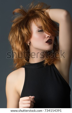 red-haired girl in a black dress on a gray background