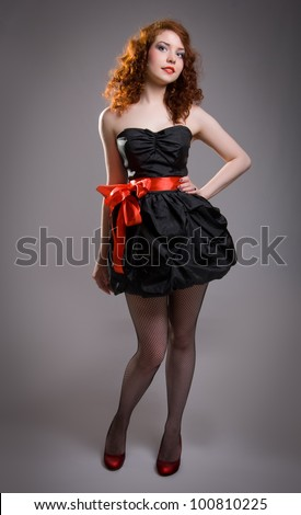 Red-haired girl in black dress - stock photo