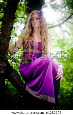red-haired girl in forest on the tree - stock photo