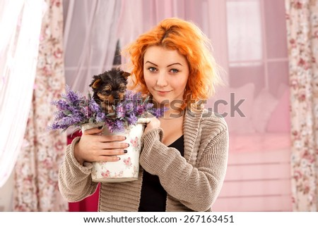 Red haired girl is holding a puppy dog and flowers. Young beautiful woman in home interior with a puppy breed York. Puppy sitting in a basket with flowers. Woman, comfort, home, happiness -  life joy. - stock photo