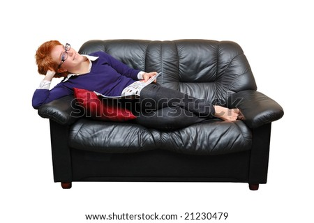 Red-haired girl is laying on sofa and reading magazine - stock photo