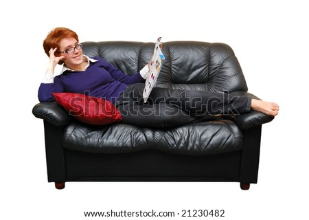 Red-haired girl is laying on sofa and reading magazine