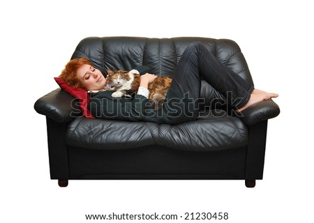 Red-haired girl is laying on sofa with cat - stock photo