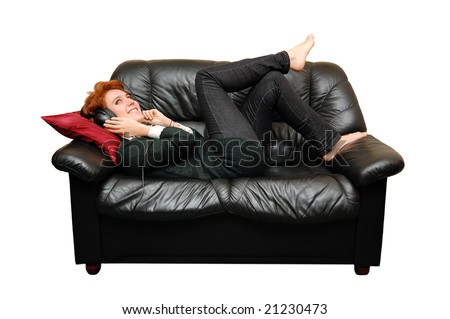 Red-haired girl is laying on sofa with headphones