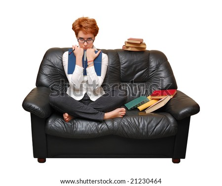 Red-haired girl is sitting on sofa with books - stock photo