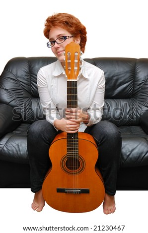 Red-haired girl is sitting on sofa with guitar - stock photo
