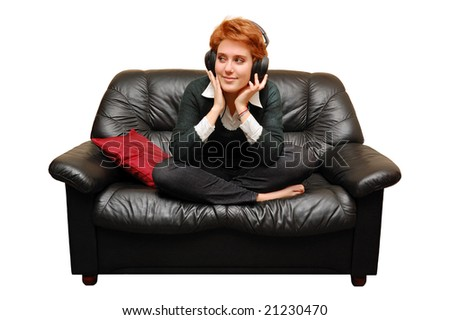 Red-haired girl is sitting on sofa with headphones - stock photo