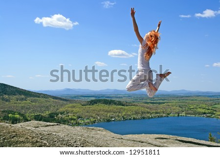 Red-haired girl jumping to the sun on the mountain. - stock photo