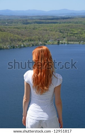 Red-haired girl looking over blue lake from the mountain. - stock photo
