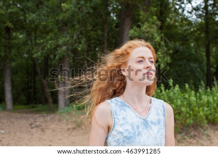 Red-haired girl on the nature. Freedom. Happiness. Success. Sexy girl near the water. Girl with long red hair. Sand.
