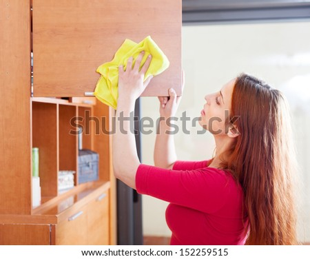 red-haired girl wiping the dust from wooden furniture at home - stock photo