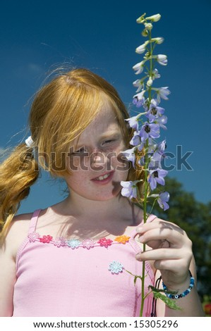 red haired girl with a blue larkspur flower - stock photo