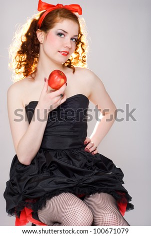 Red-haired girl with red apple - stock photo