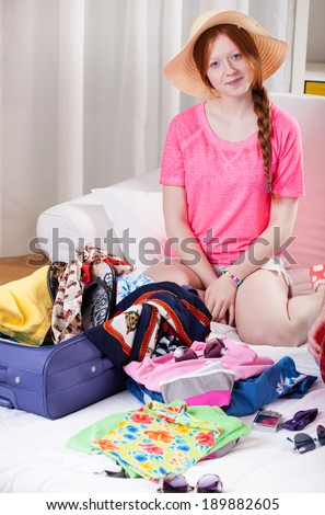 Red haired girl with straw hat during travel preparation - stock photo