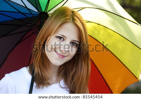 Red-haired girl with umbrella in autumn season.