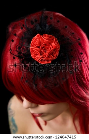Red haired gothic girl with black feather hair fascinator and red roses - stock photo