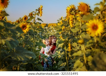 Red-haired mother and her little son playing in beautiful sunflowers field. Image with selective focus - stock photo