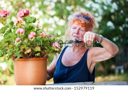 Red-haired pensioner working in the garden