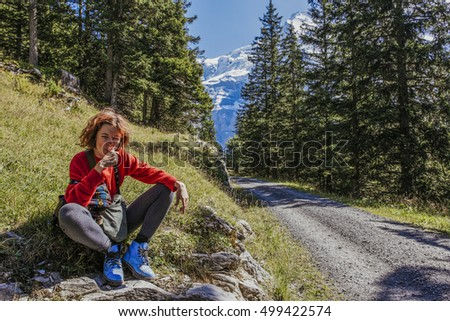 Red haired, pretty, european girl is brushing her teeth in the mountains in the morning. Switzerland
